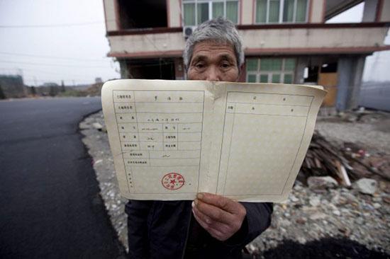 propietario cinese con casa in mezzo alla strada